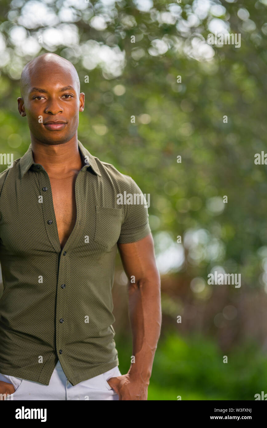 Portrait of a man posing partially off frame. Young African American male model in a nature scene blurry background - Stock Image