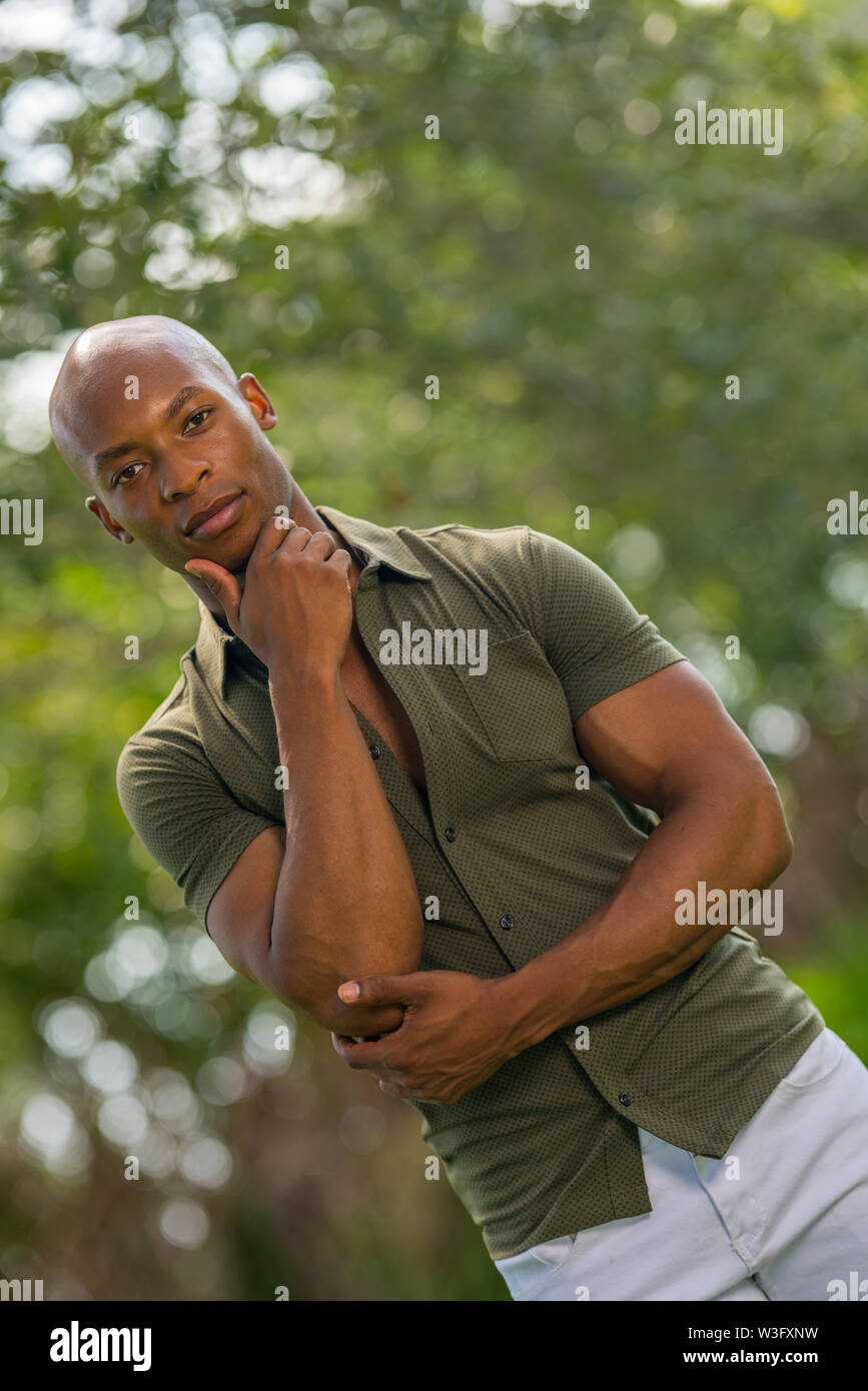Nature scene with handsome male model posing with hand under chin - Stock Image