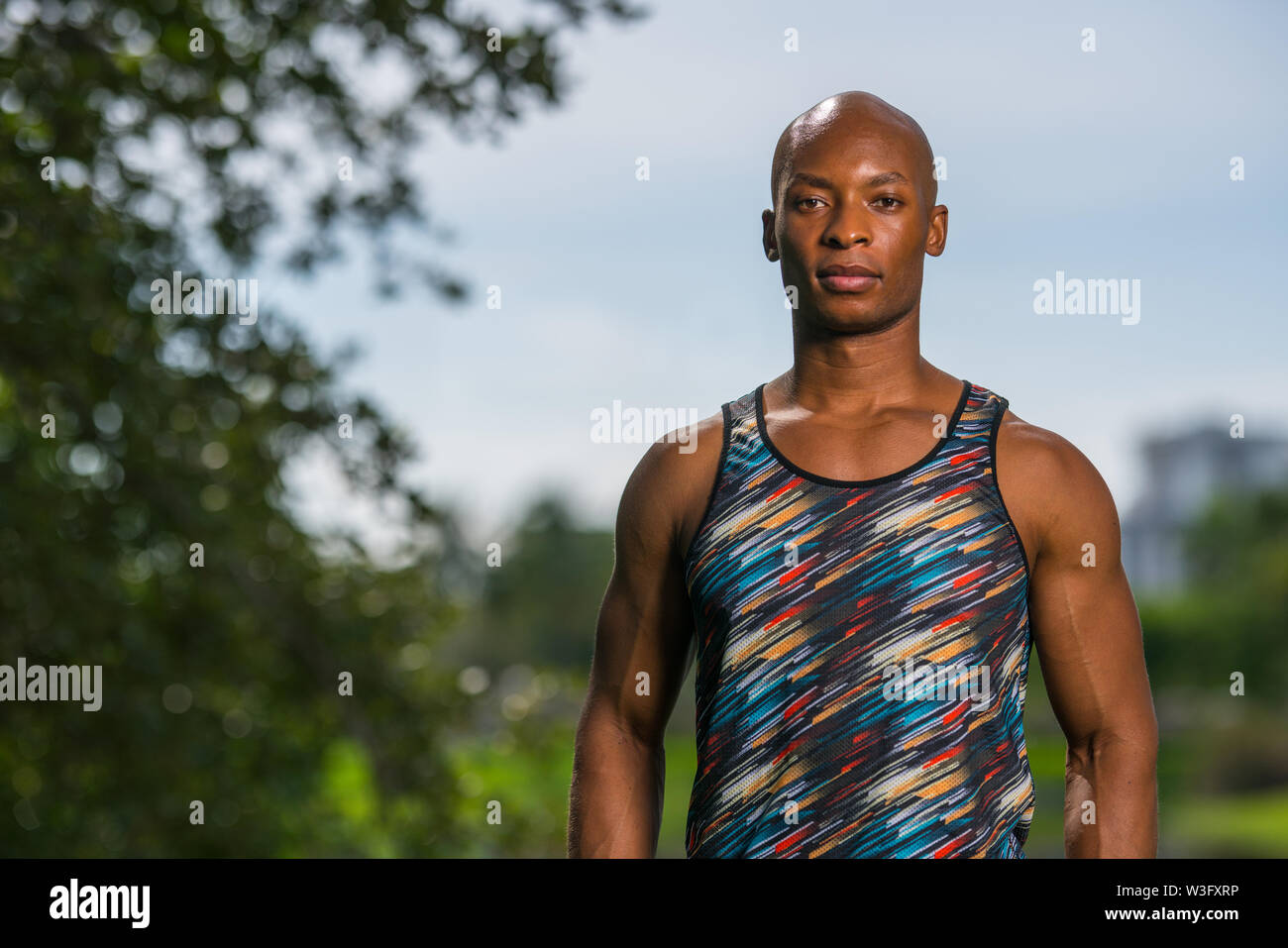 Portrait of an athletic black man with abstract colored shirt posing outdoors in a park - Stock Image