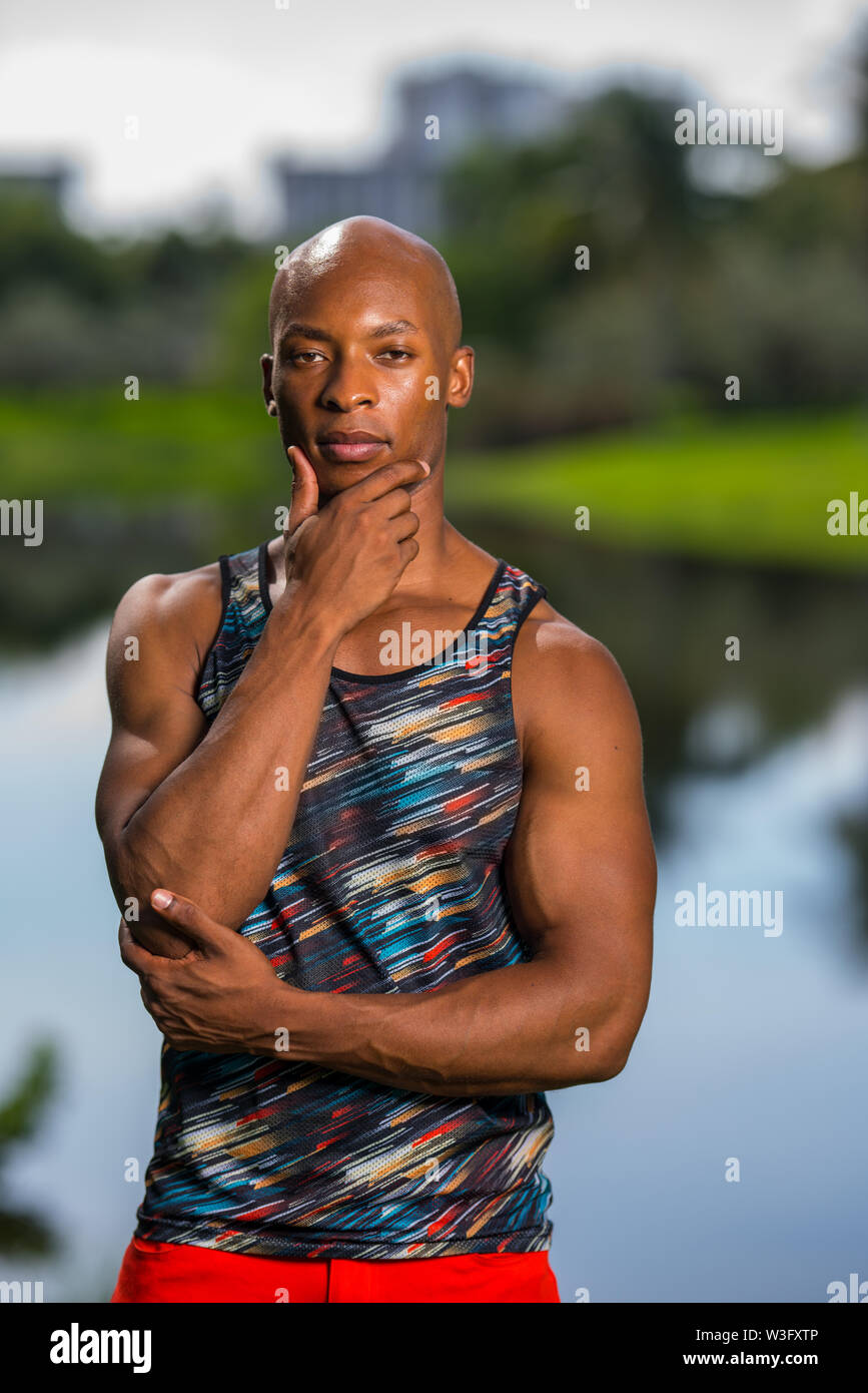 Portrait of a handsome man posing with hand under chin. African American athletic person with a tank top shirt. - Stock Image