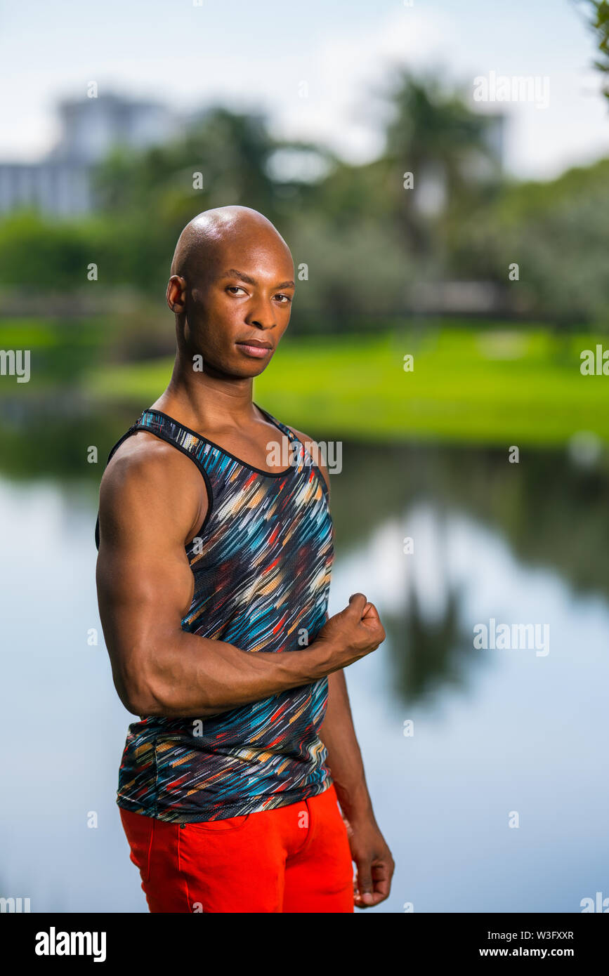 Portrait of a handsome black male fitness model flexing his arm. Posing in an outdoor park scene with lake in background - Stock Image