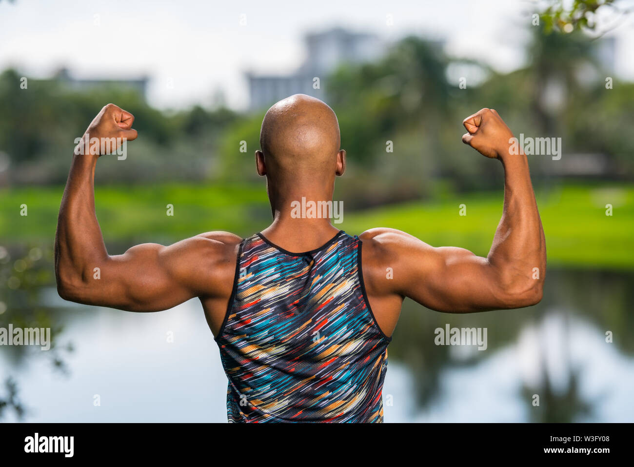 Rear view portrait of a strong macho man flexing his arms. Park lake scene in the background - Stock Image