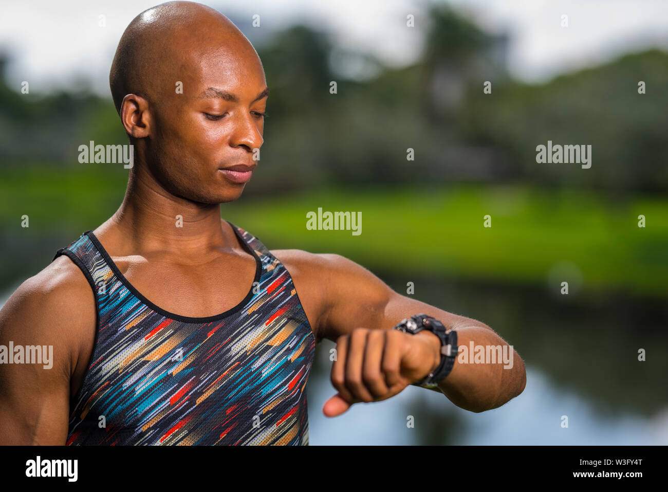 Portrait of a African American fitness model looking at his smartwatch - Stock Image