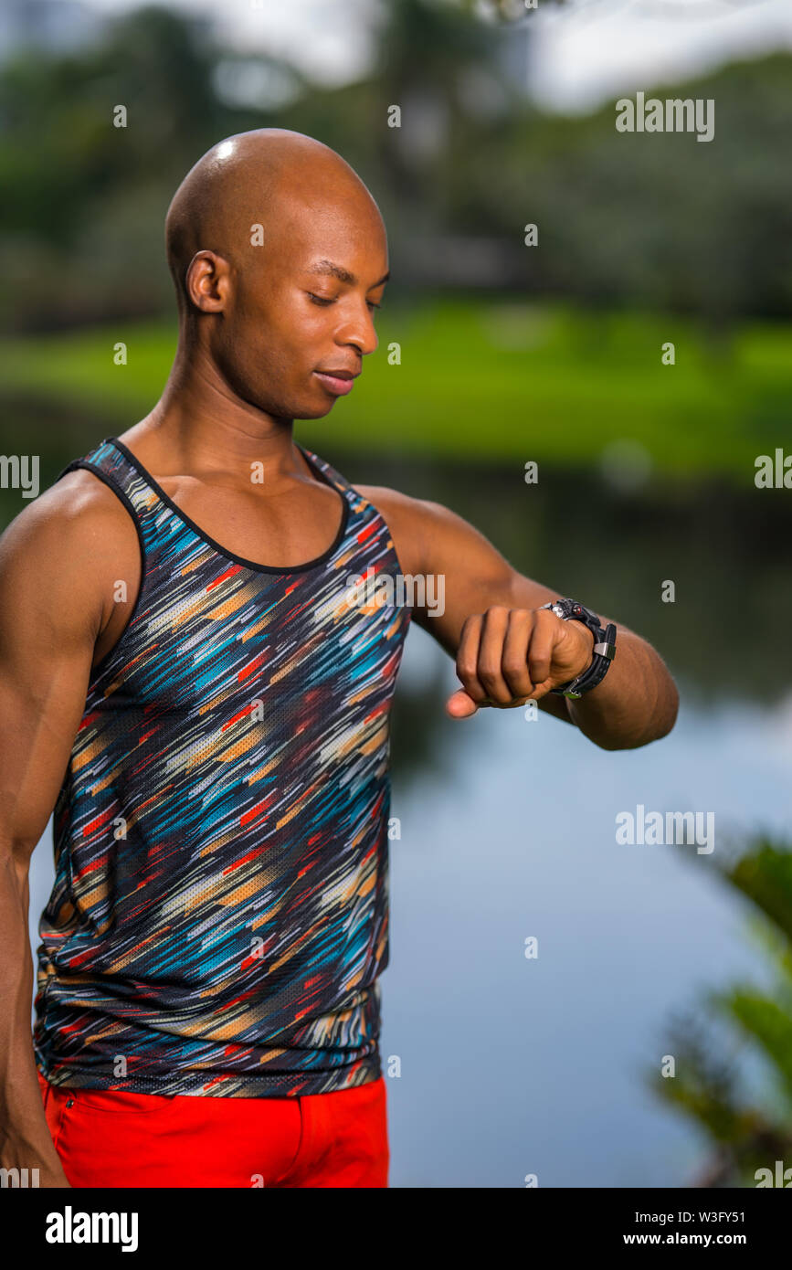 Image of a healthy fitness model looking at this smart watch. Image shot outdoors in nature setting lit with off camera flash - Stock Image