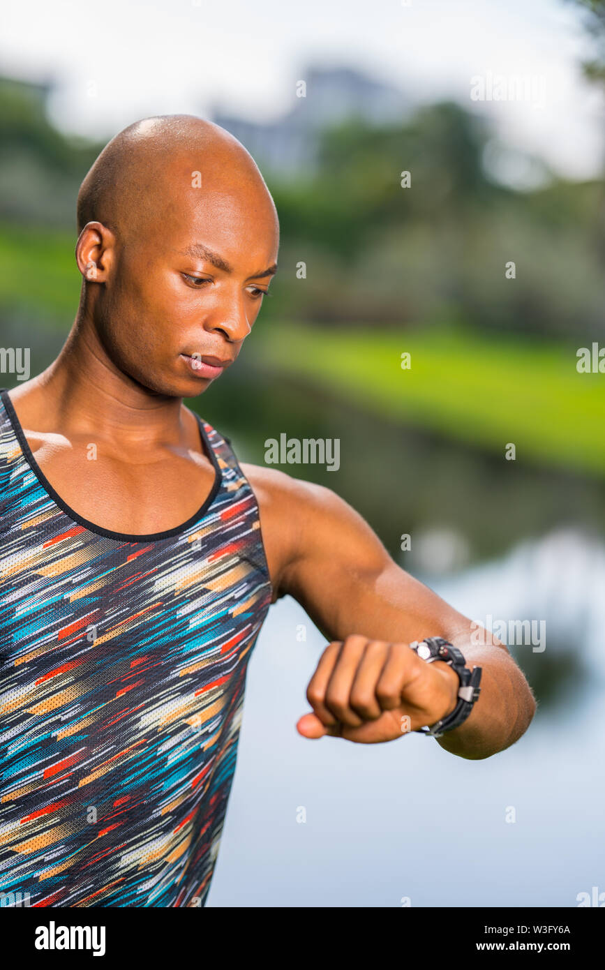 Photo of a fitness model looking at his smartwatch with confused expression - Stock Image