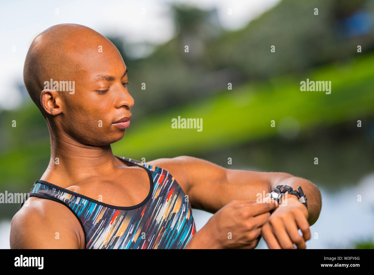 Photo of a fitness model setting his smart watch settings - Stock Image