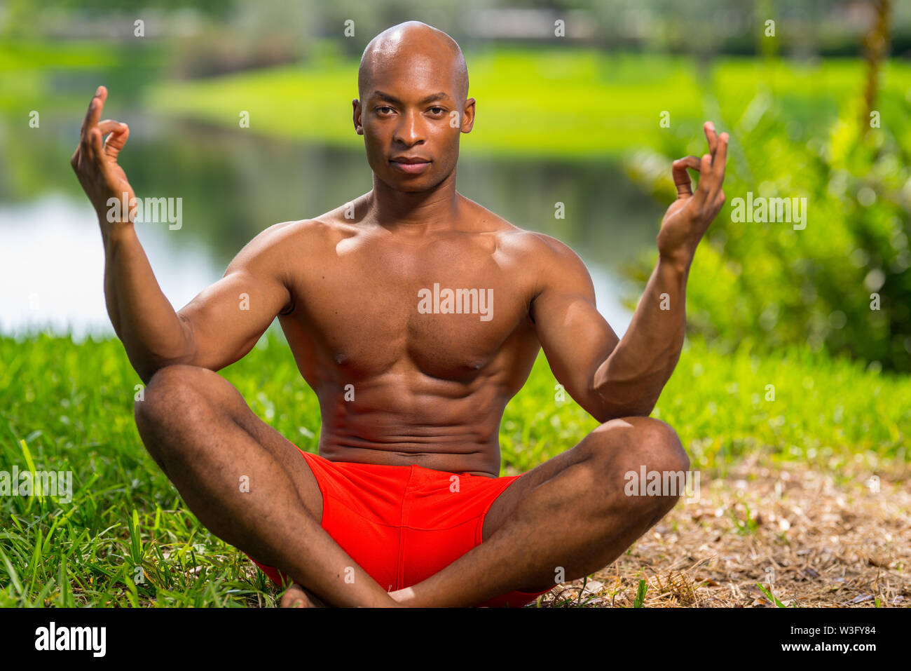 Photo of a fitness model in a yoga pose. Image lit with flash in a park setting - Stock Image