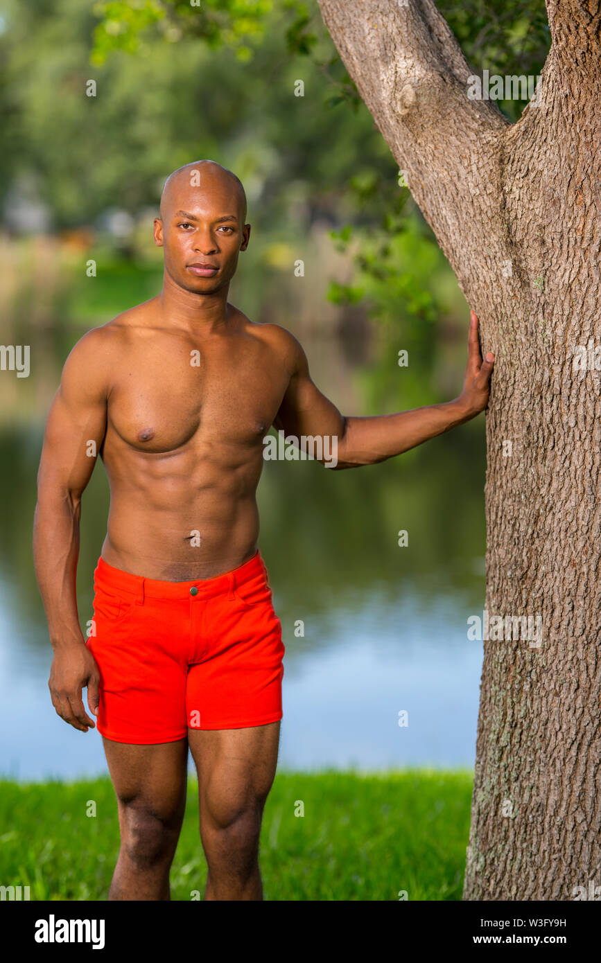 Fitness model posing in bright red shorts at a park setting. Image lit with off camera flash - Stock Image