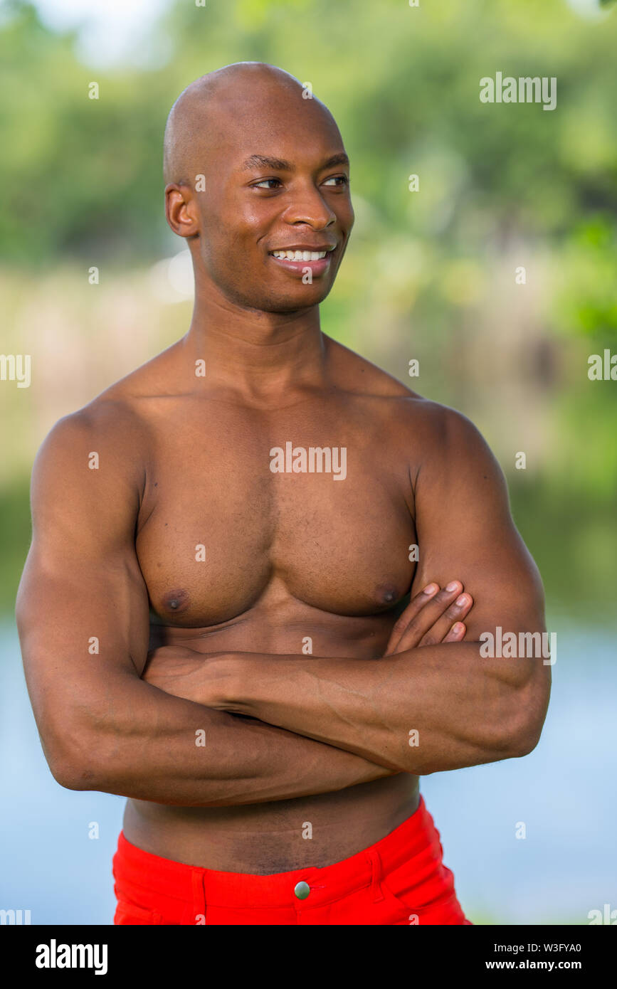 Portrait of a fitness model with no shirt smiling off camera. - Stock Image