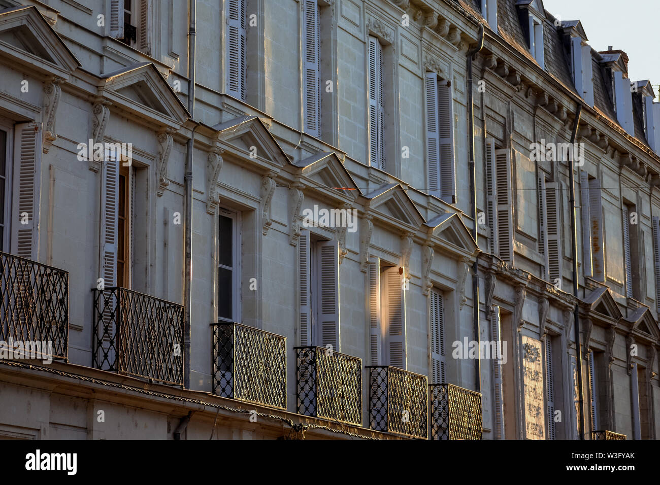 French Building ancient facade at sunset. - Stock Image