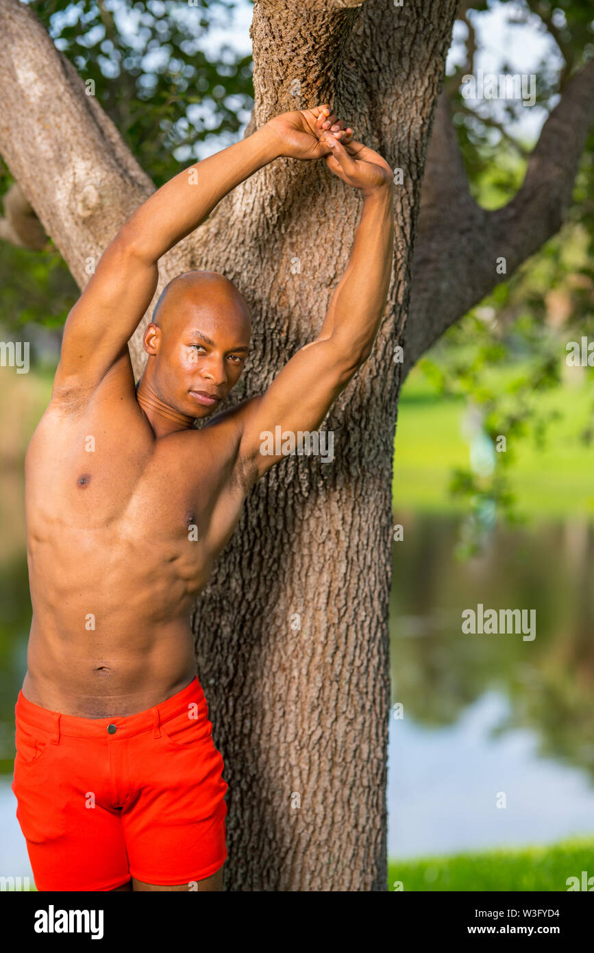 Photo of a young African American fitness model stretching in the park. Man posing shirtless showing muscles. LIt with off camera flash - Stock Image