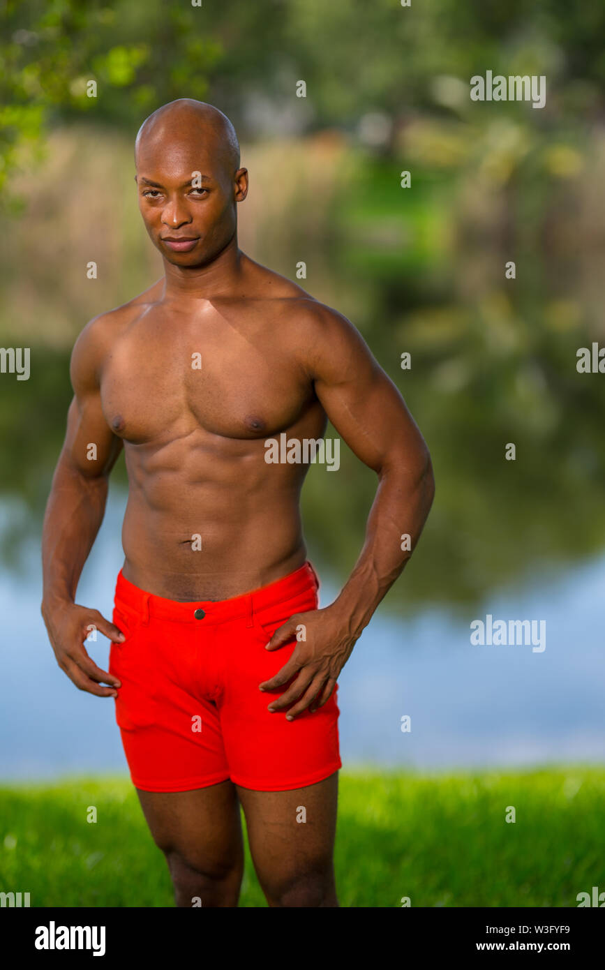 Photo of a handsome fitness model with big muscles. Image lit with off camera flash - Stock Image