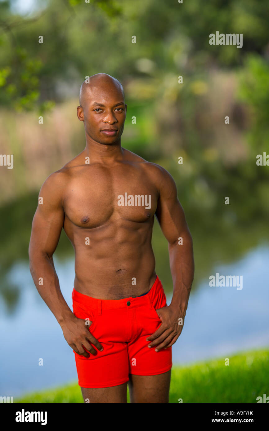Photo of a shirtless fitness model posing outdoors lit with off camera flash - Stock Image