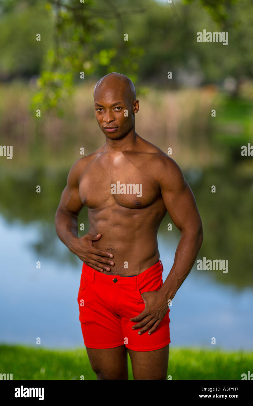 Handsome African American fitness model posing shirtless in the park. Lit with off camera flash - Stock Image