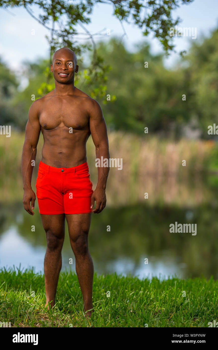 Portrait of a handsome young man smiling in the park. Fitness model shirtless lit with off camera flash - Stock Image