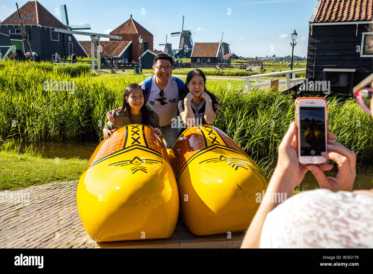 Zaanse Schans, Netherlands, historical village, open-air museum in North Holland, old windmills, workshops, farms, houses, tourists, souvenir photo in - Stock Image