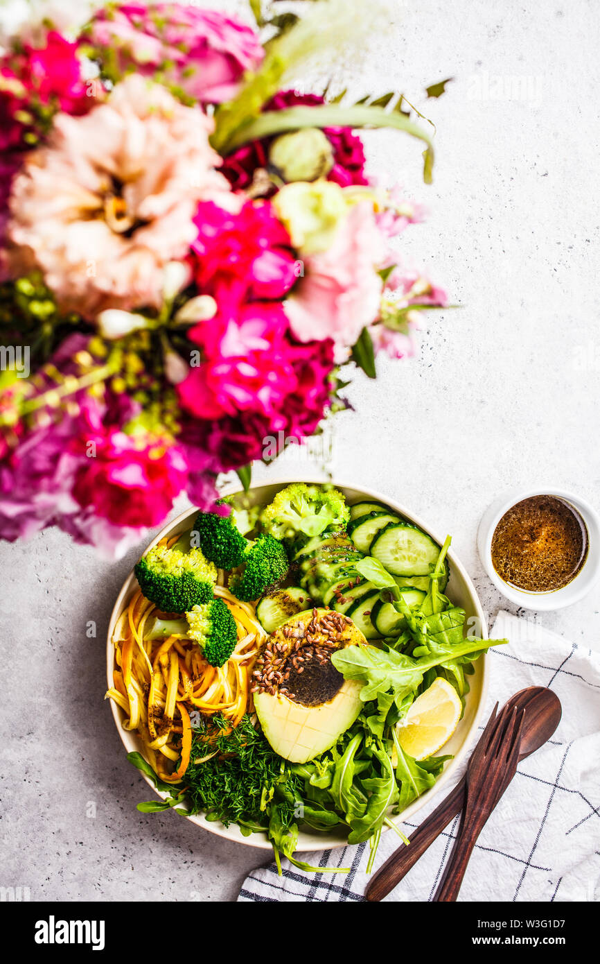 Green salad with broccoli, zucchini pasta, avocado and dressing. Plant based diet concept. Summer food background. - Stock Image