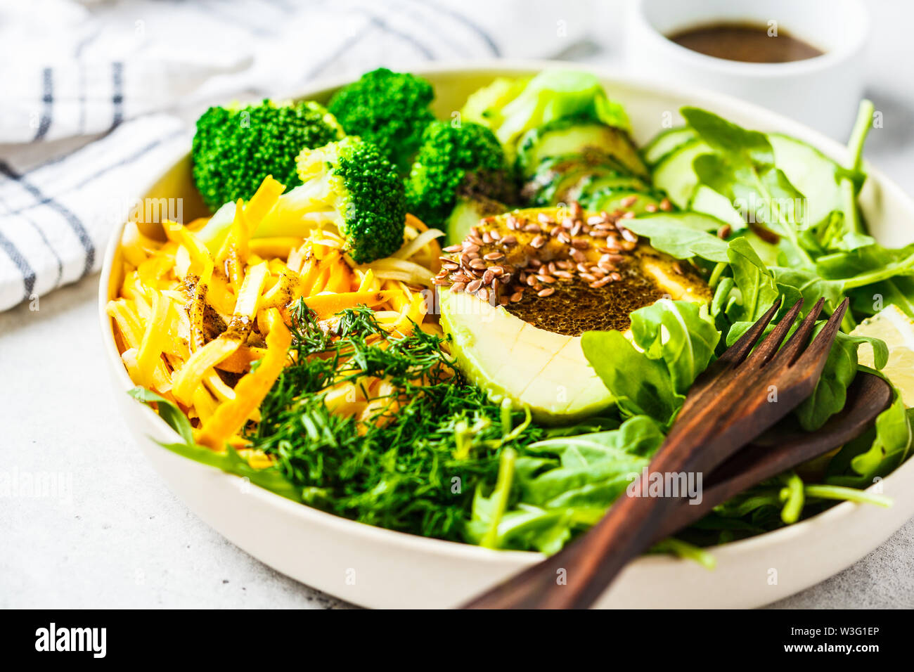 Green salad with broccoli, zucchini pasta, avocado and dressing. Plant based diet concept. - Stock Image