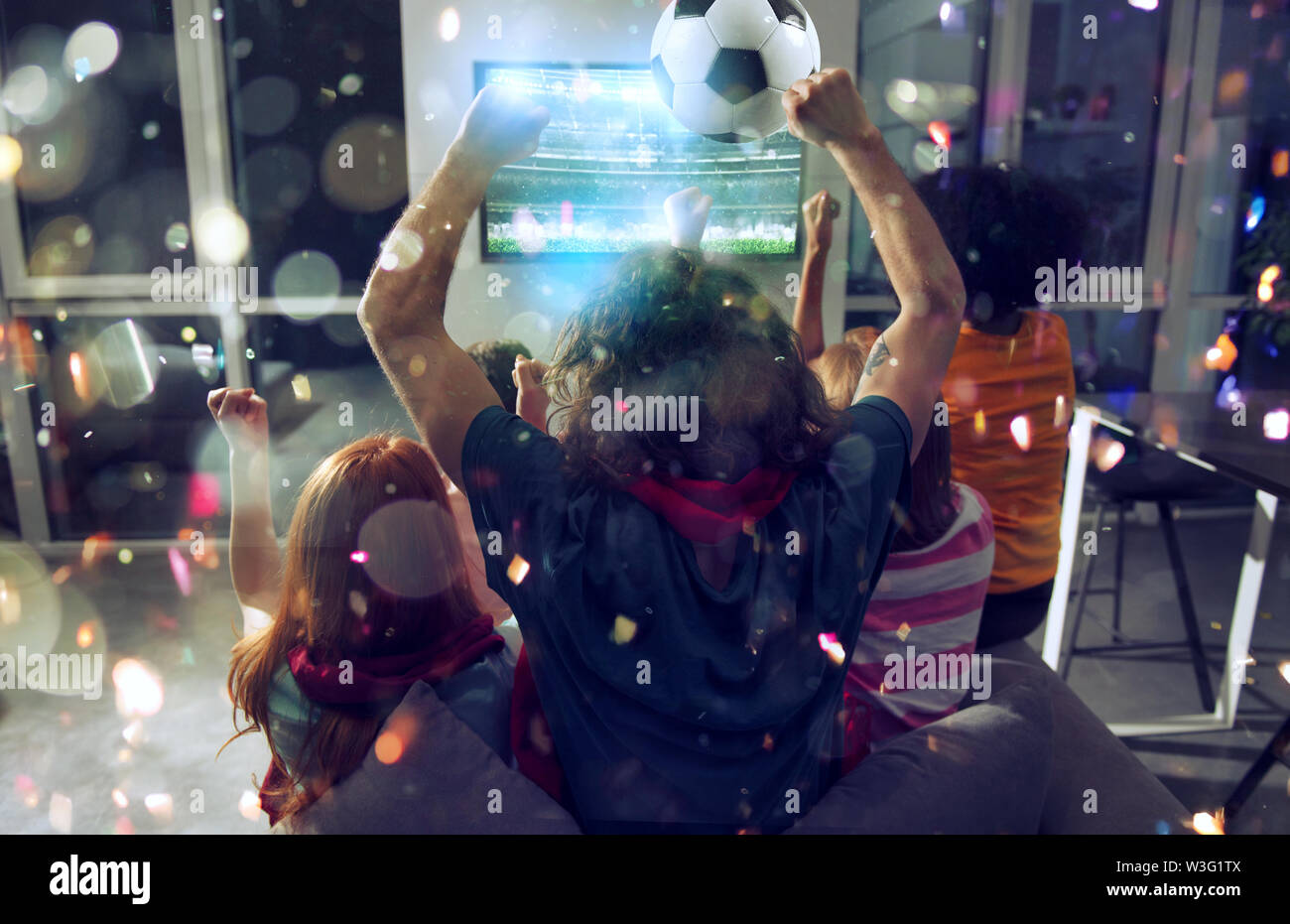 Happy friends of football fans watching soccer on tv and celebrating victory with falling confetti. Double exposure - Stock Image