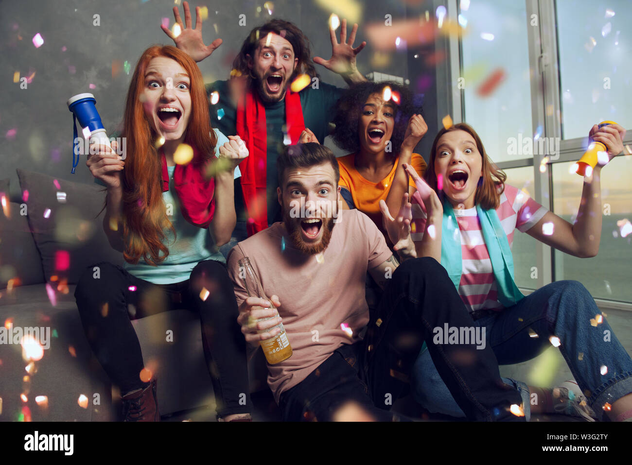 Happy friends of football fans watching soccer on tv and celebrating victory with falling confetti. - Stock Image