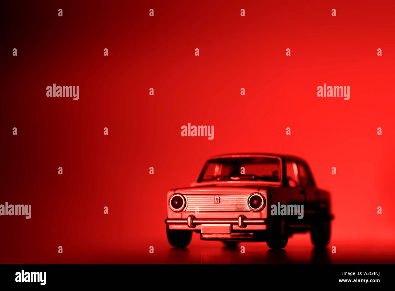 Front view of a retro car toy car on a red background. - Stock Image