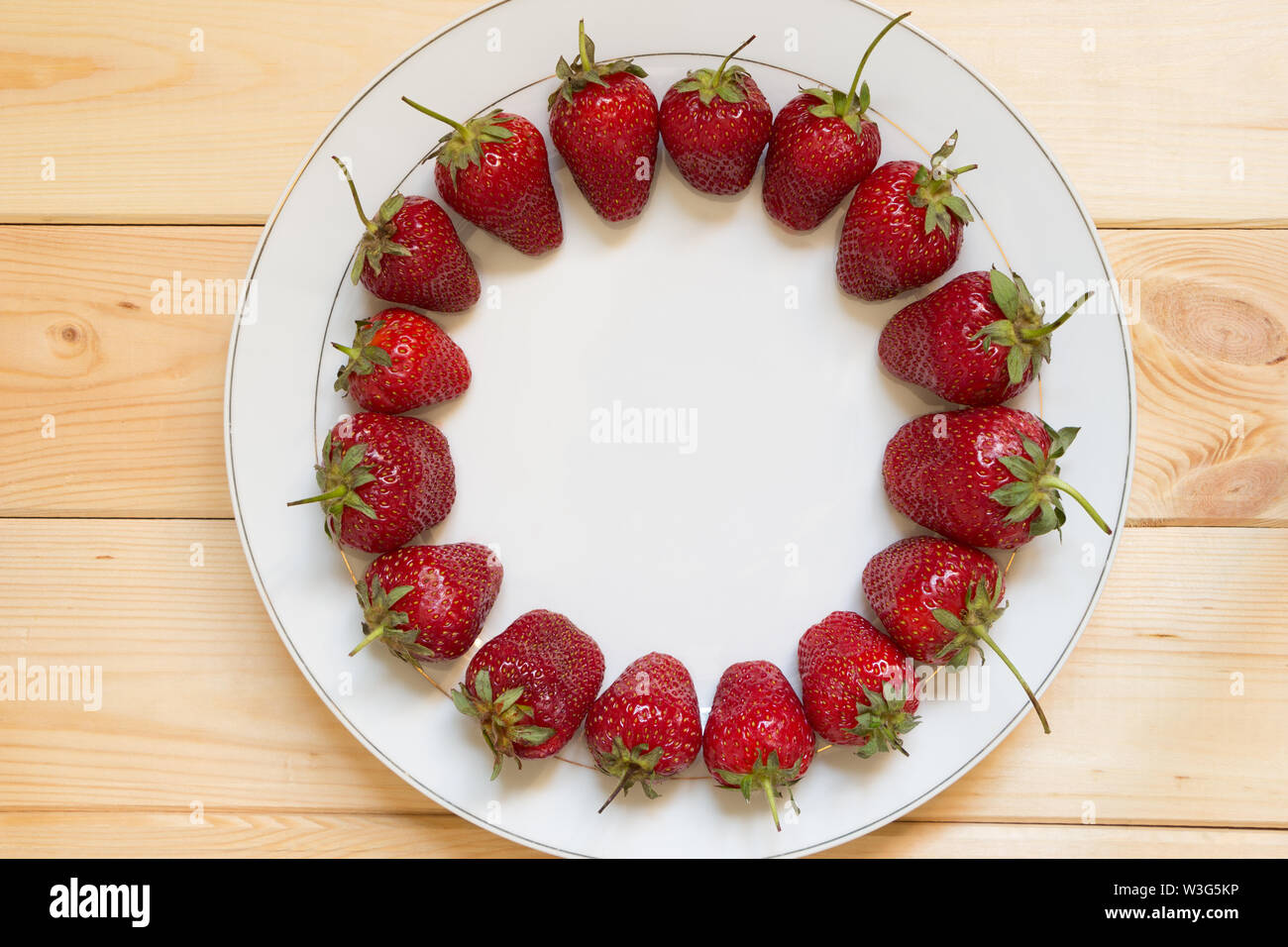 Red ripened strawberries laid out in circle shape on white plate on light wooden table. Copy space in center of frame. Place for text. Delicious natur Stock Photo