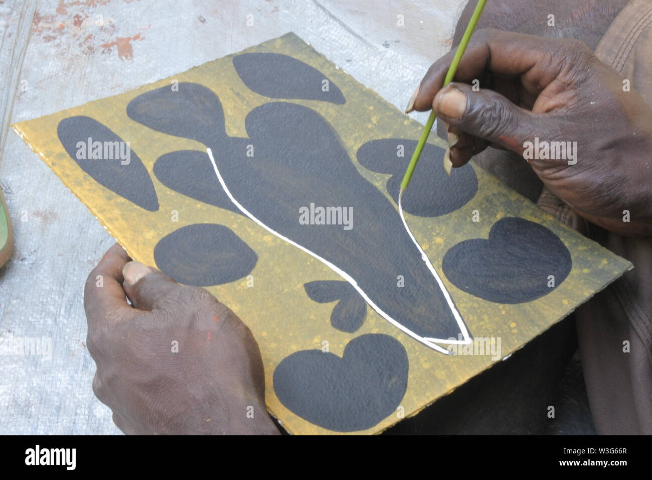 Aboriginal artist dot painting. Aboriginal artists eliminating the sacred elements and abstracting their paint into dot Stock Photo