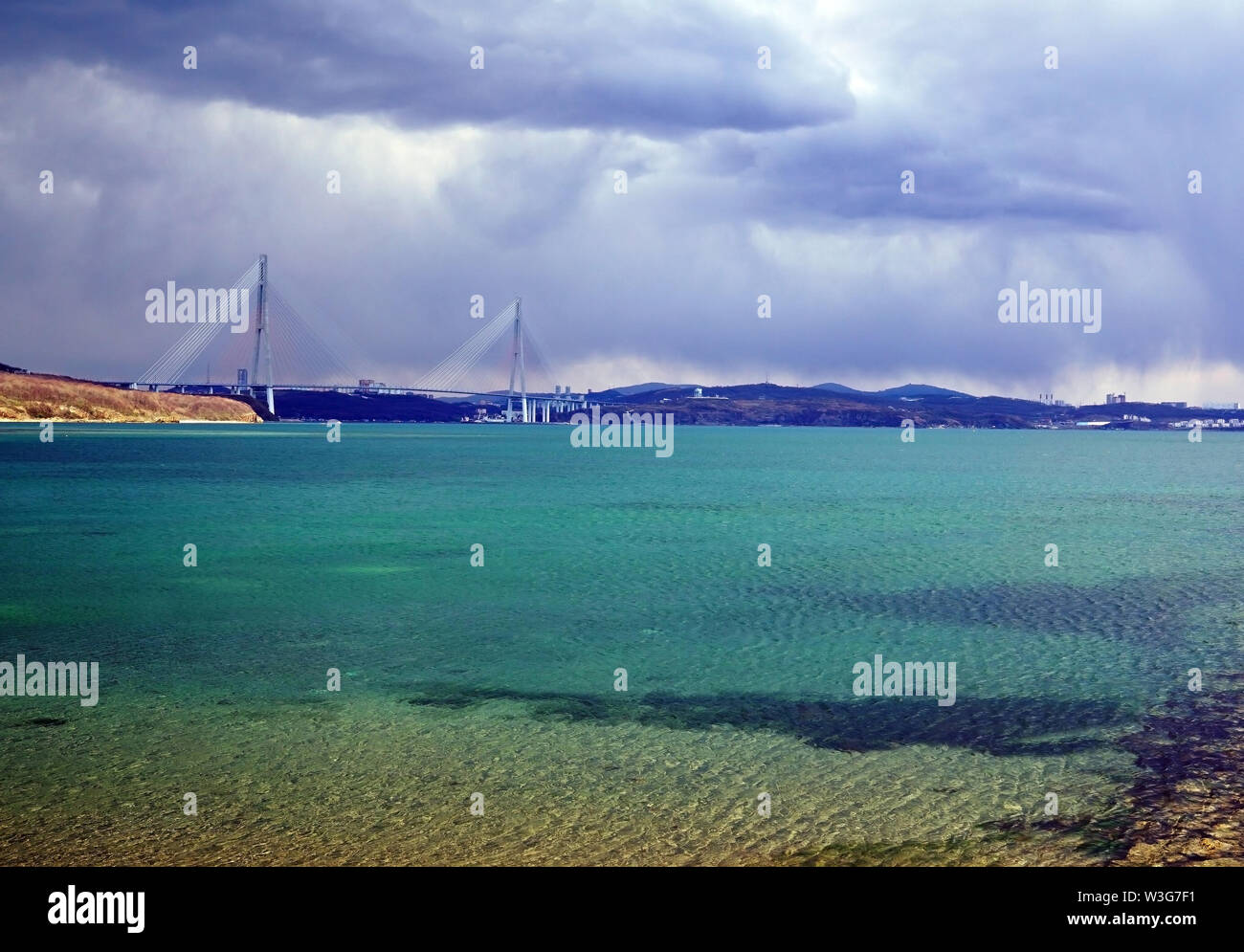 Turquoise sea lagoon on the background of the cable-stayed bridge. A storm begins above the bay, the sky is overcast. Russia, Vladivostok, island Russ - Stock Image