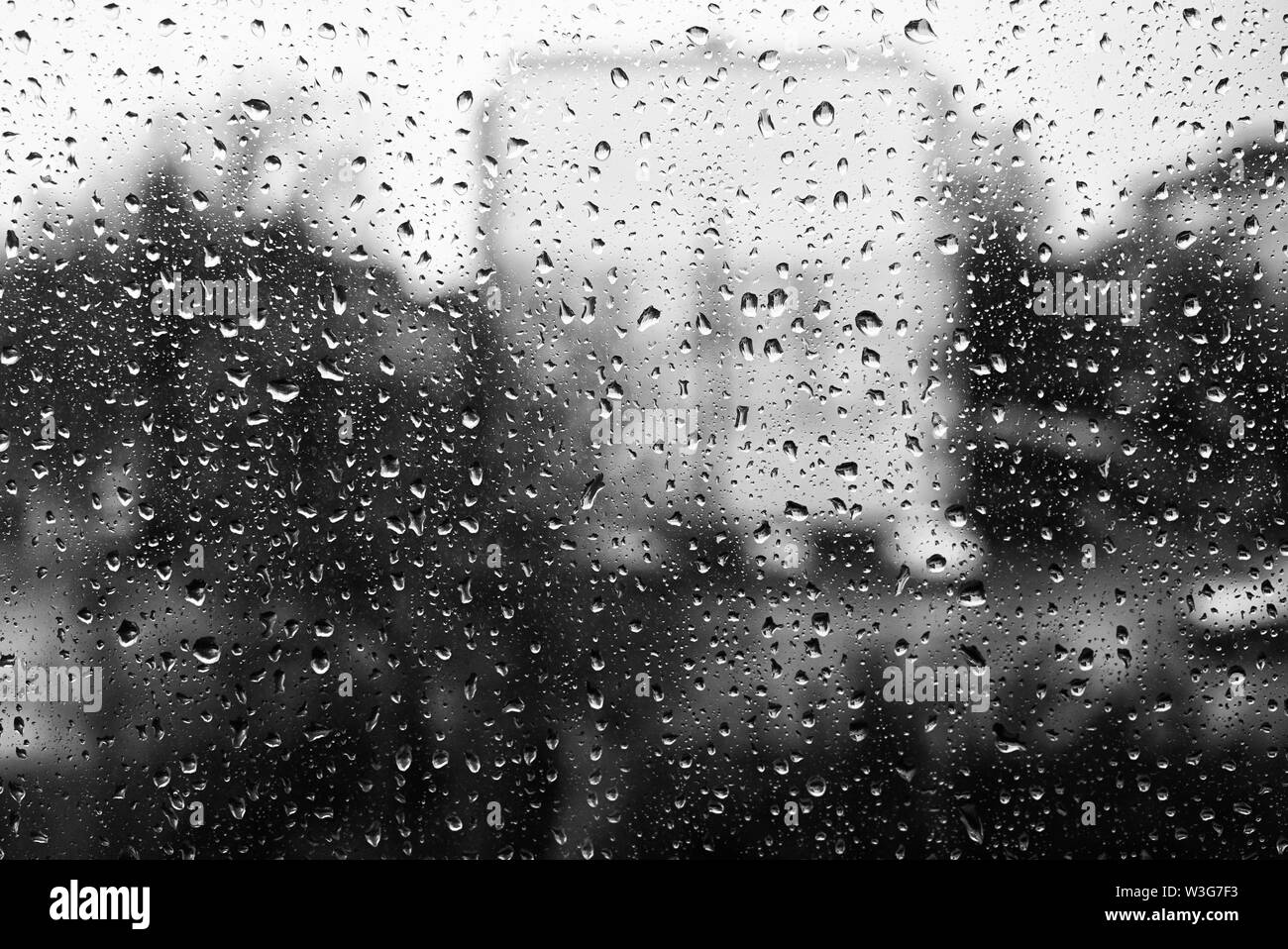 Black and white photo of droplets on the glass. Behind the glass building silhouette - Stock Image