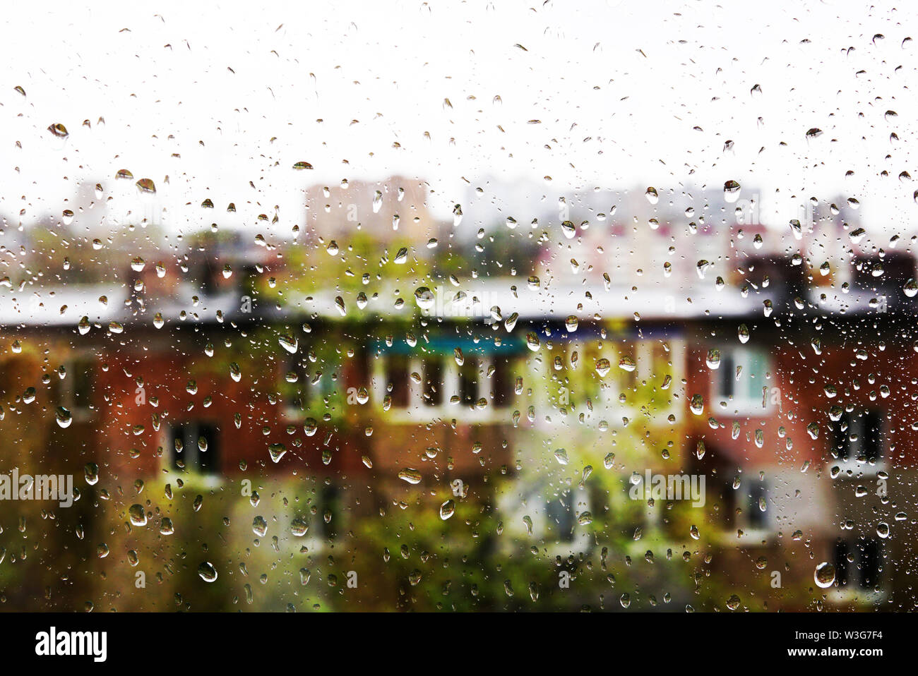 Drops of water on the window glass. Behind the glass silhouettes of buildings with windows - Stock Image