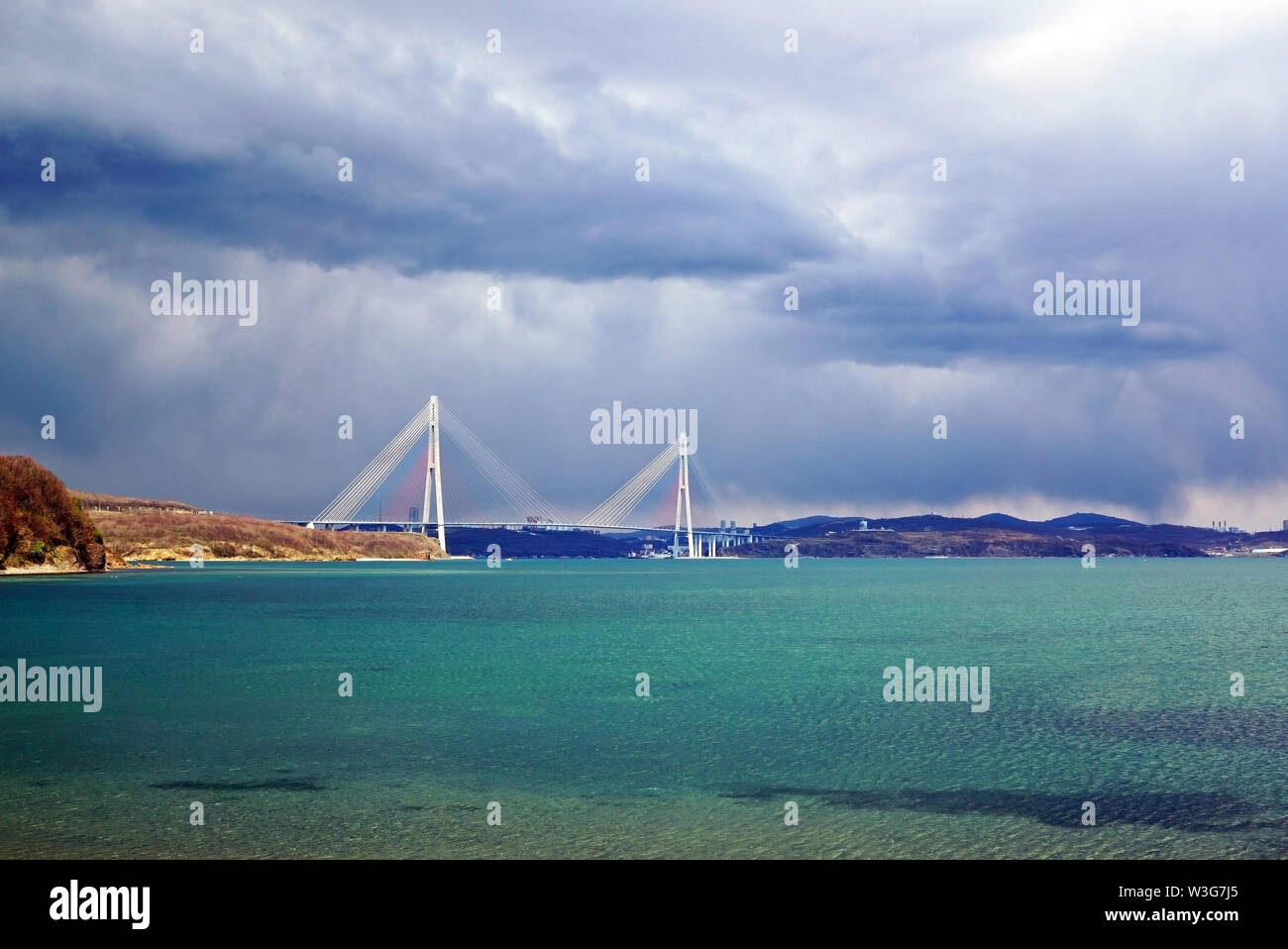 Bay by the sea with turquoise water. In the background cable stayed bridge. Stormy sky overcast. Russia, Vladivostok, island Russian - Stock Image