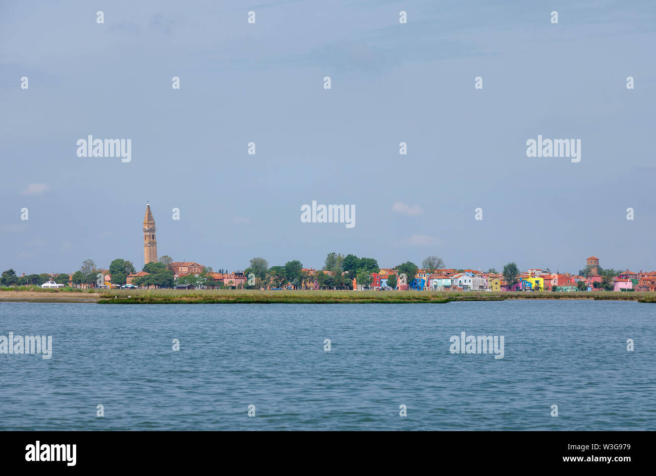 View of Burano, a small island in Venice Lagoon, Italy with the leaning campanile of the Church of San Martino on the skyline and coloured houses - Stock Image