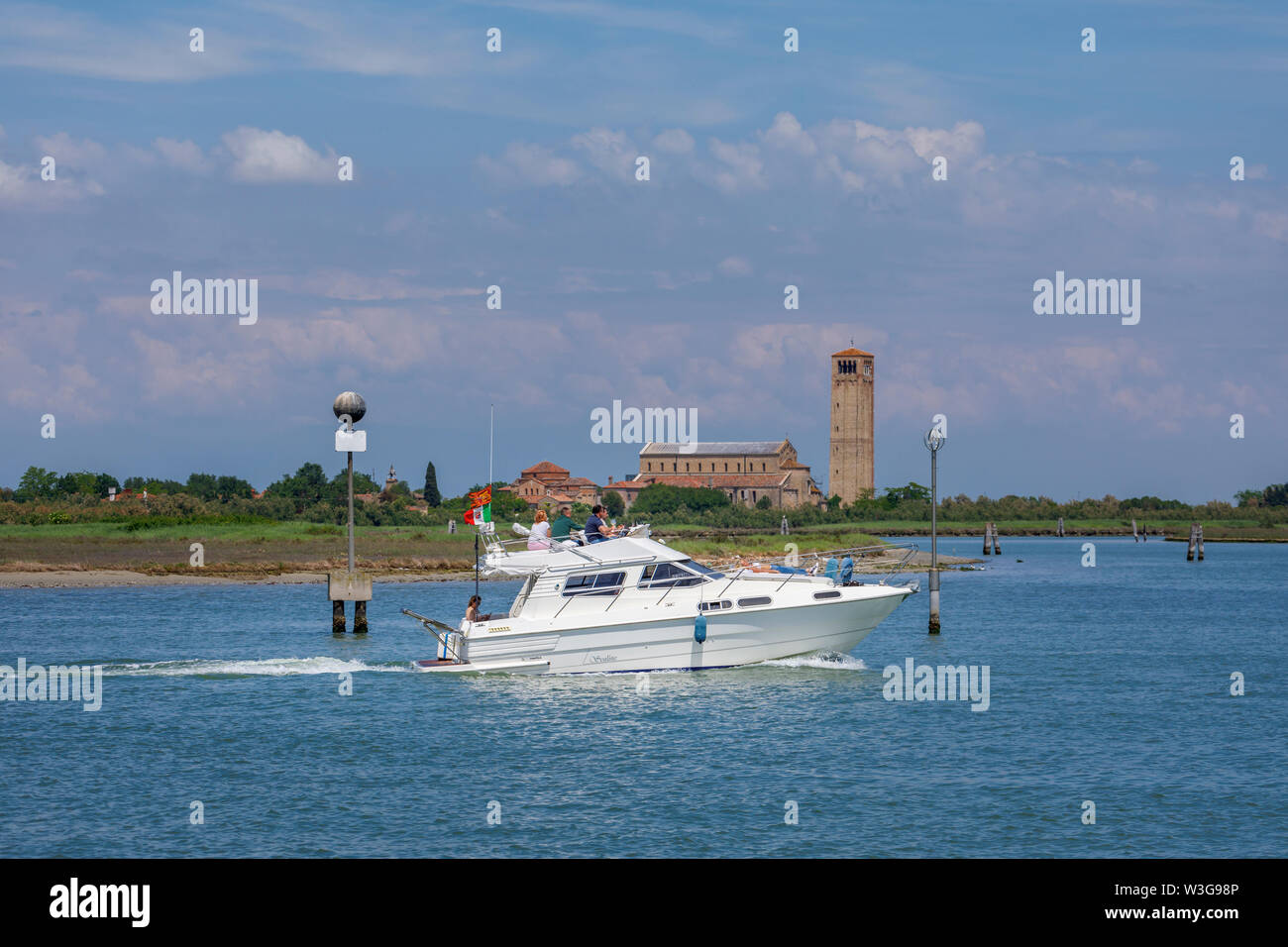 White speedboat speeding by Torcello, a small island in Venice Lagoon, Italy: view of Cathedral of Santa Maria Assunta, Santa Fosca and campanile - Stock Image
