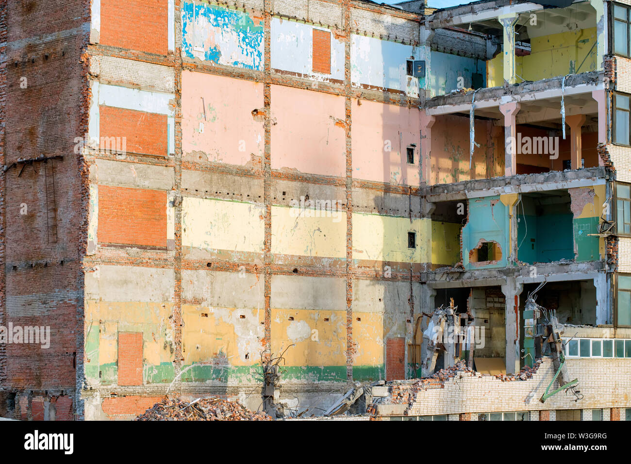 Partially destroyed industrial building with colored walls. Demolition or destruction theme - Stock Image
