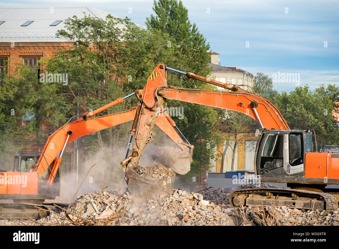 Two orange excavators working on the debris of a demolished building. Cleaning the rubble, building demolition and clearing site theme image - Stock Image