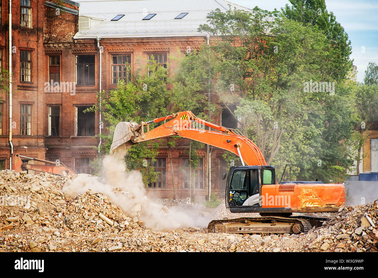 Orange excavator working on the ruins of a demolished building. Cleaning the rubble, building demolition and clearing site theme image - Stock Image