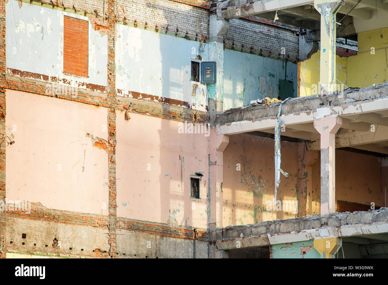 Modern partially destroyed industrial building with colored walls. Demolition or destruction theme - Stock Image