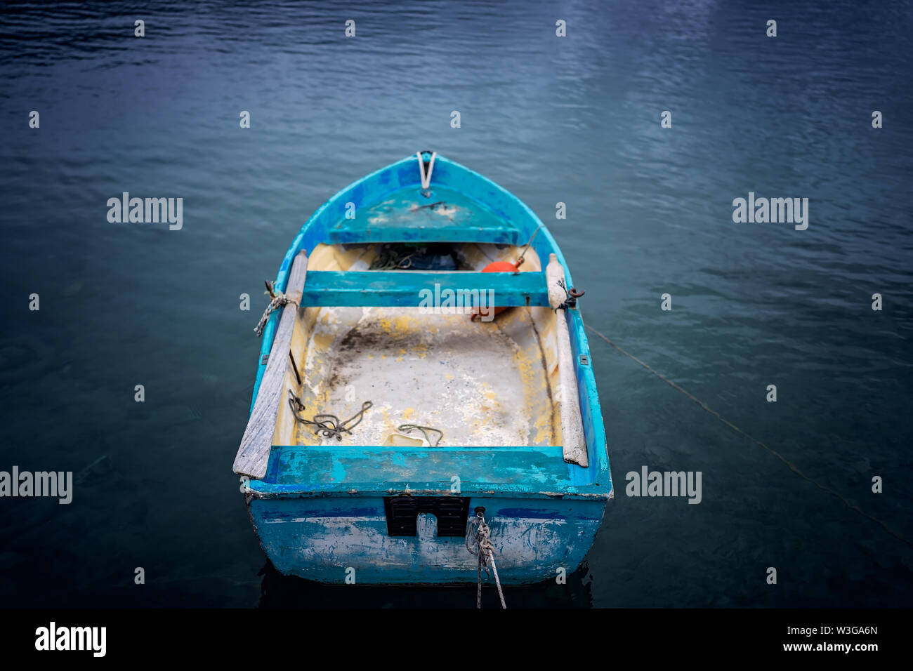 Small blue wooden rowing fisherman boat in the port and harbour in the Alykes Bay in Zante, Greece Stock Photo