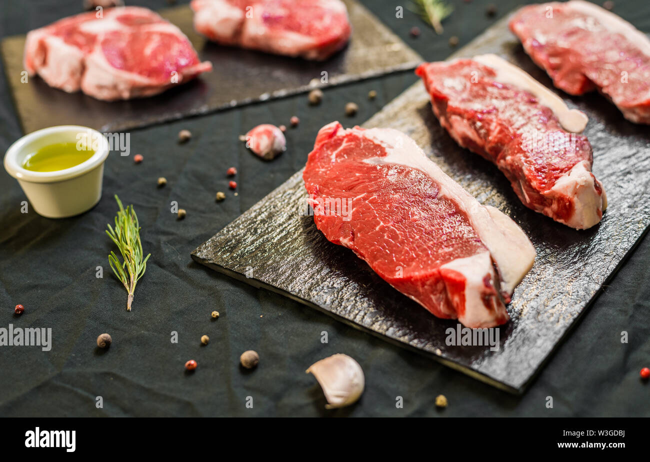Beef cow meat steaks with spices and herbs against black background - Stock Image