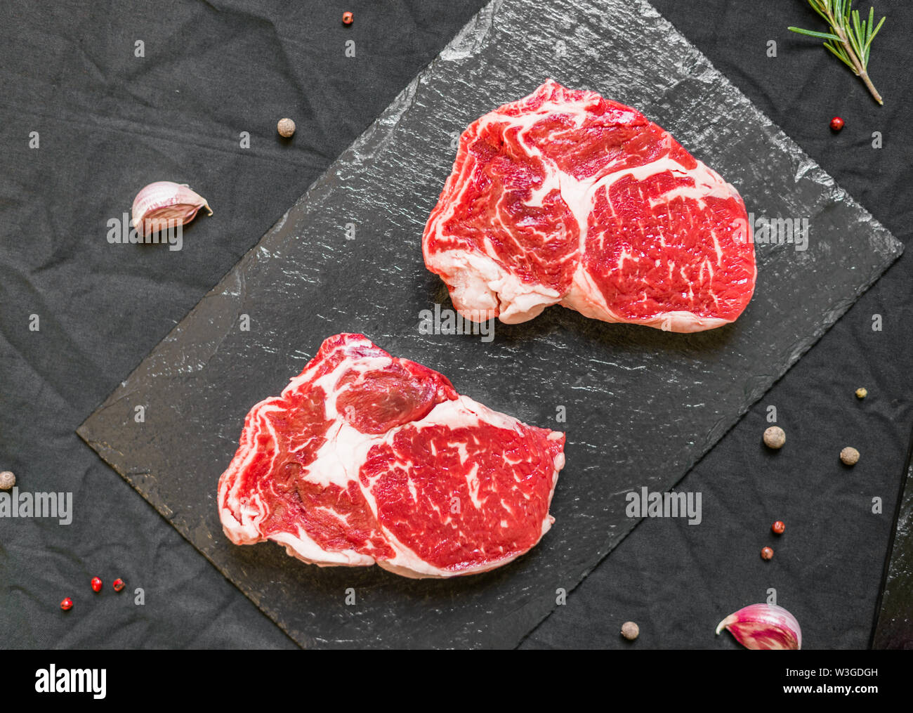 Rib eye beef cow steak meat with spices and herbs against black background - Stock Image