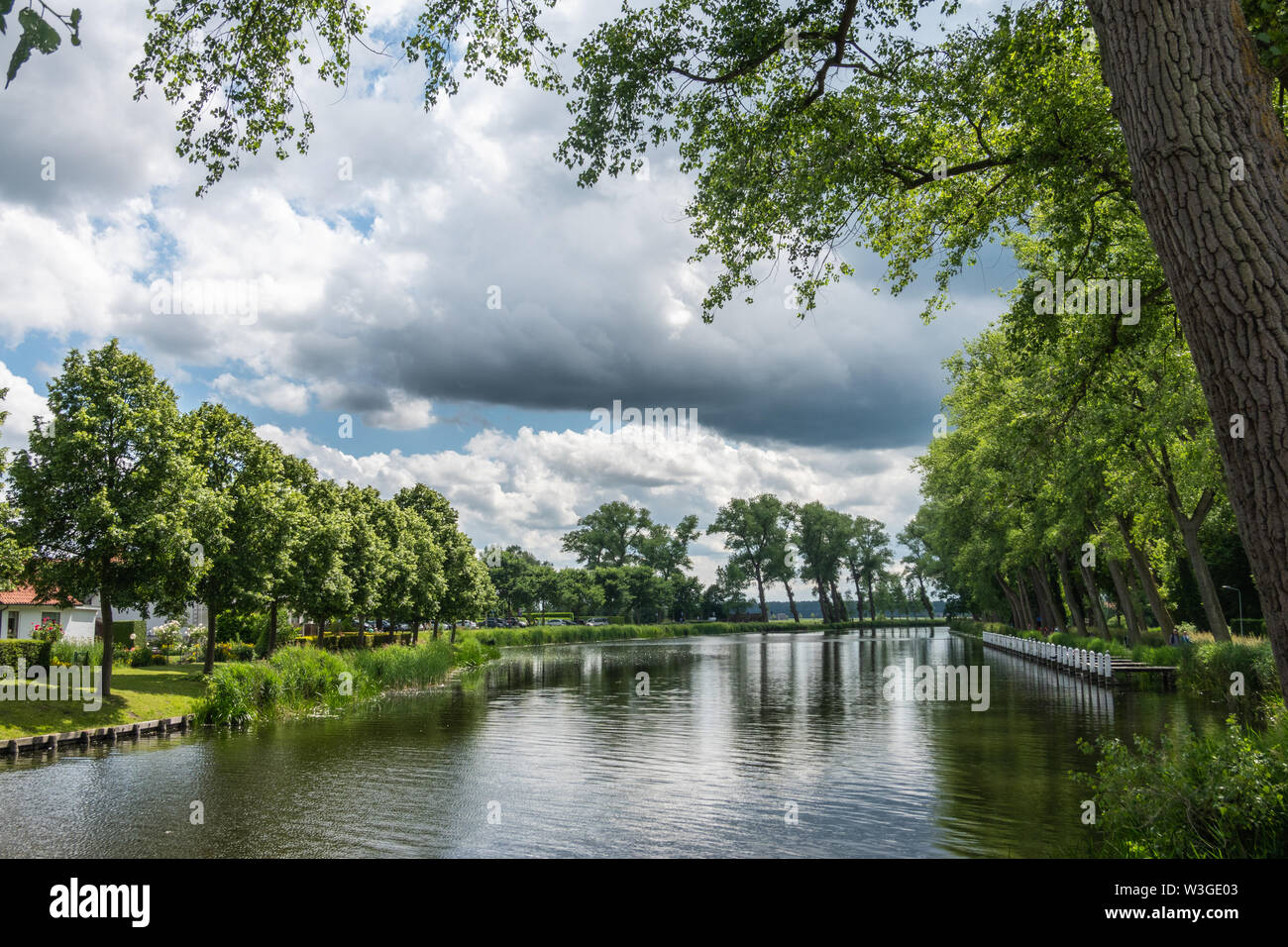 Sluis, the Netherlands -  June 16, 2019: Reflecting water of canal to Damme in Belgium, with curtains of green trees on sides, under a storm approachi - Stock Image