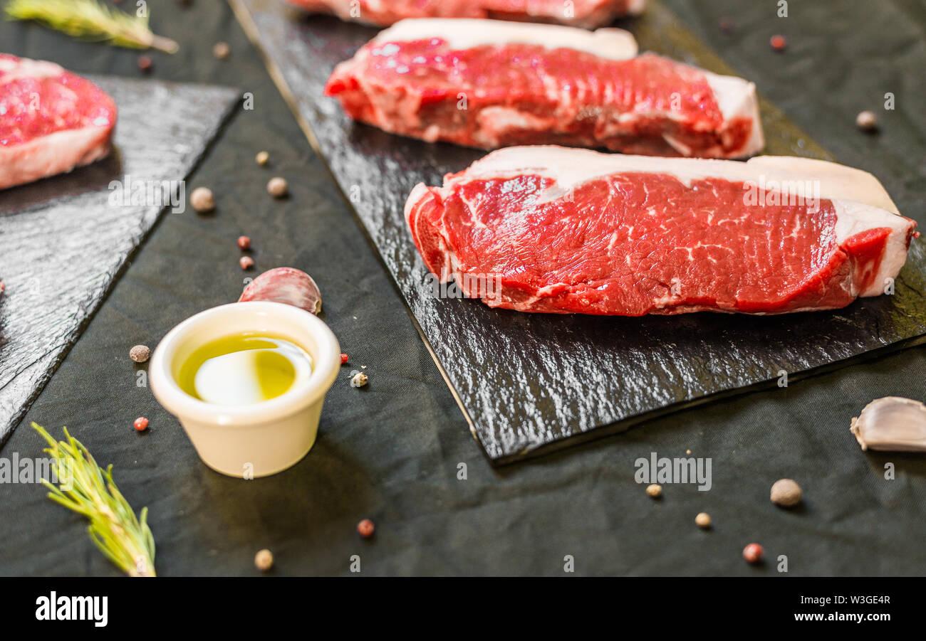 New york strip porterhouse steak beef meat against black background - Stock Image