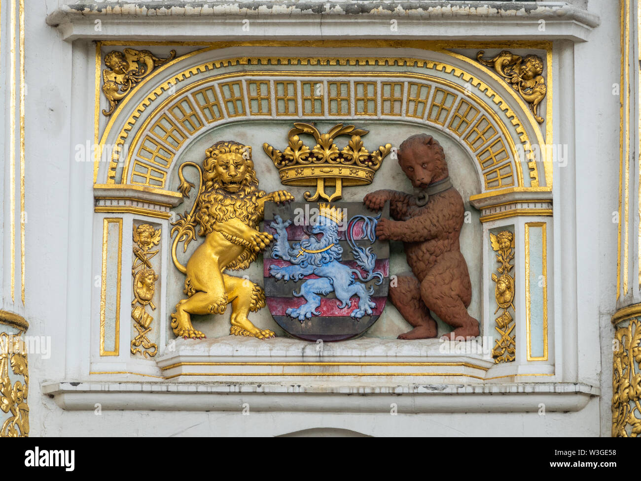 Bruges, Flanders, Belgium -  June 16, 2019: Coat of arms of the city with gold, blue, white, black and brown images of lion and bear. Set in facade. - Stock Image