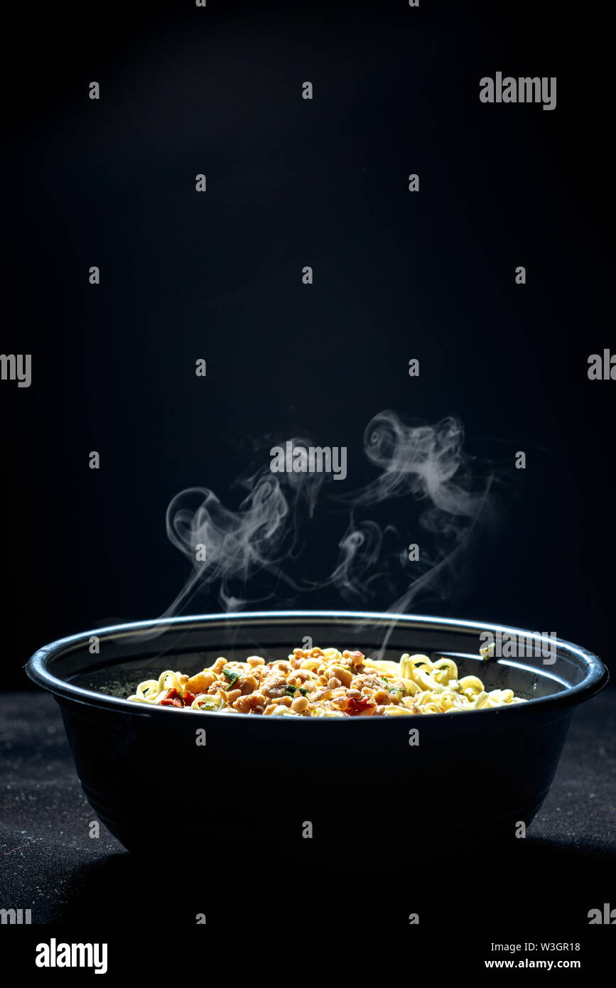 Noodles on the bowl over black background - Stock Image