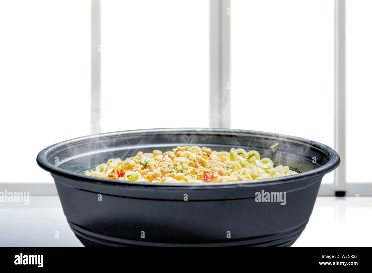 Noodles on the bowl on table with window glass background - Stock Image