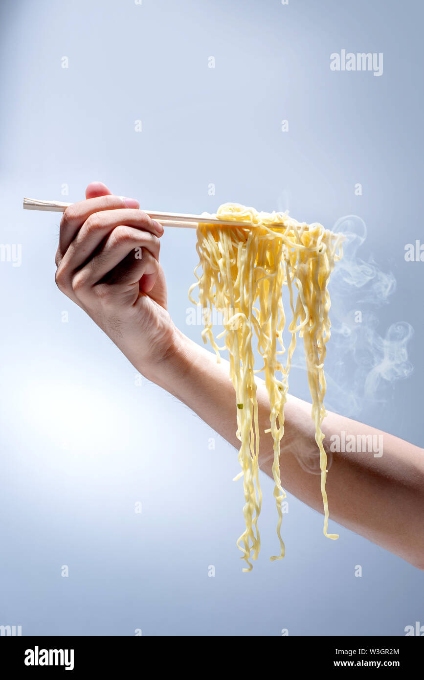 People eat the noodles with chopsticks over bright background - Stock Image
