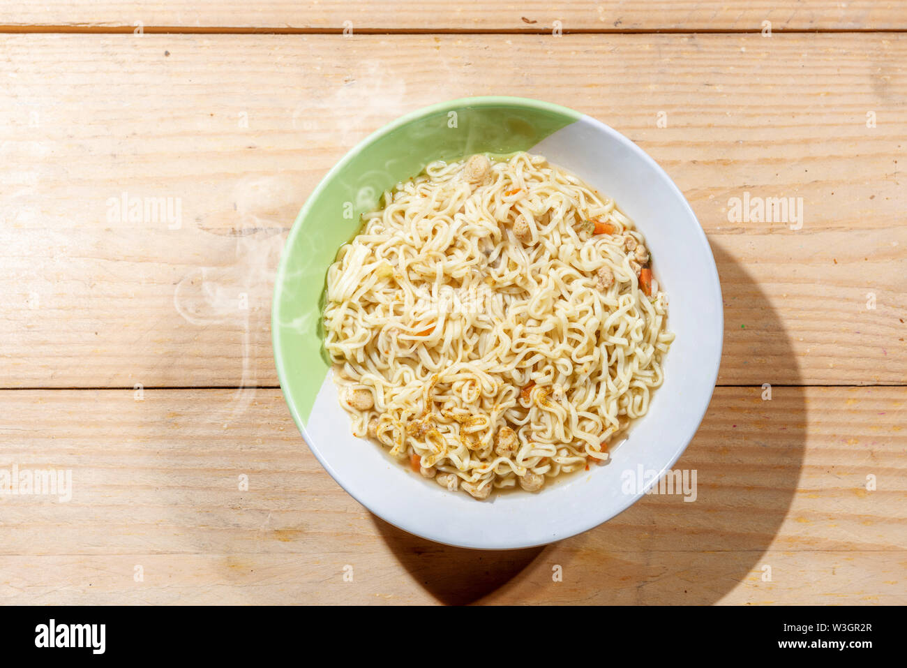 Noodles on the bowl on wooden table background - Stock Image