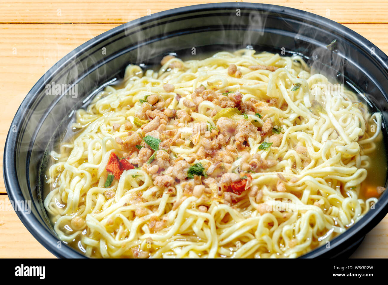 Close up of noodles on the bowl on wooden table background - Stock Image