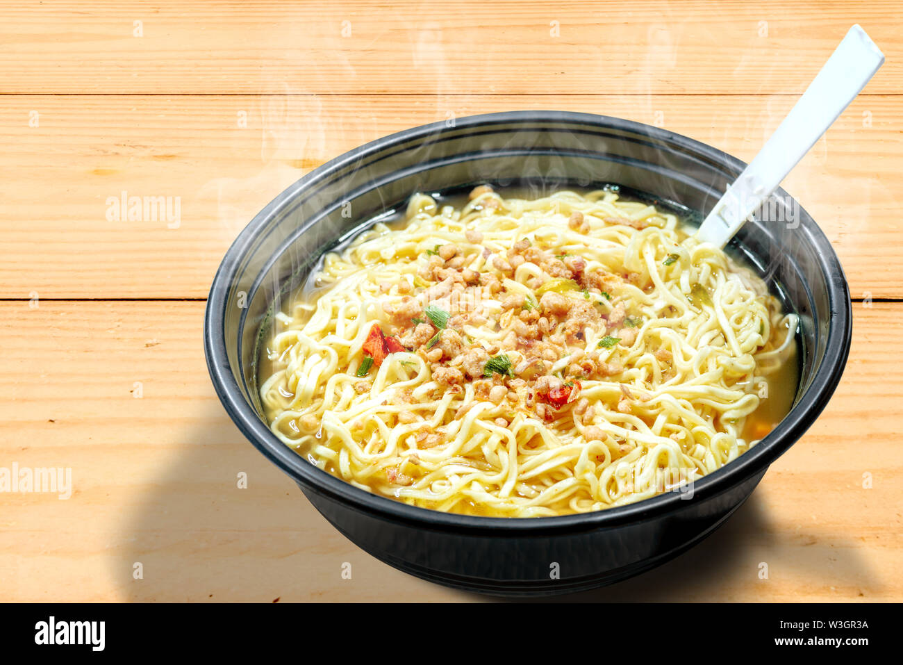 Noodles on the bowl with fork on wooden table background - Stock Image