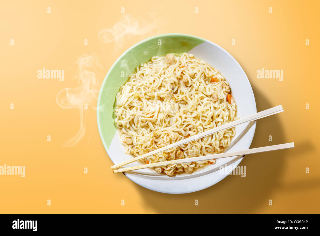 Noodles on the bowl with chopstick on yellow background - Stock Image